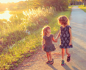 Happy kids walk hand in hand by the lake at sunset