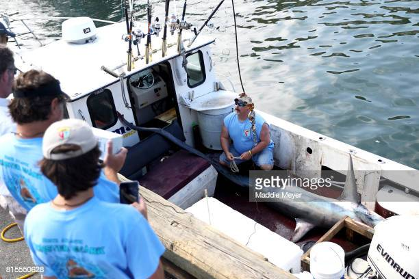 Event organizer DJ Stetson prepares to weigh a common thresher shark during the North Atlantic Monster Shark Tournament at State Pier 3 on July 15...