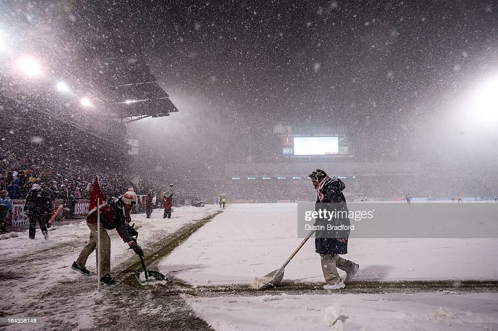 Event staff clear snow near the corner of the field even as play continues in the snow during a FIFA 2014 World Cup Qualifier match between Costa Rica and United States at Dick's Sporting Goods Park on March 22, 2013 in Commerce City, Colorado.