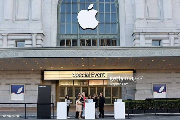 Event staff look at a computer in front of an Apple logo outside Bill Graham Civic Auditorium on September 9 2015 in San Francisco California Apple...