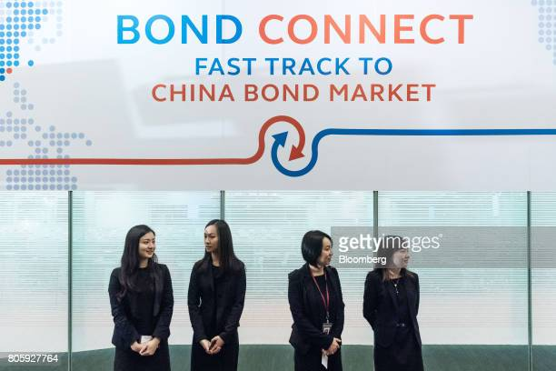 Event staff stand under signage for the ChinaHong Kong Bond Connect at the Hong Kong Stock Exchange in Hong Kong China on Monday July 3 2017 The...
