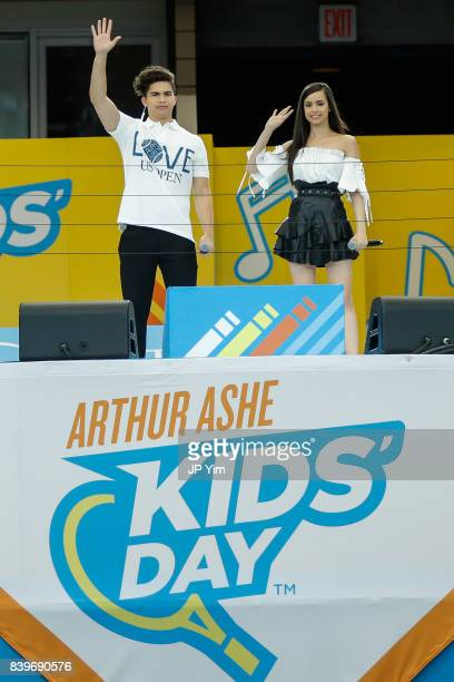 Events cohosts and singers Alex Aiono and Sofia Carson wave to the audience at the 22nd Annual Arthur Ashe Kid's Day event at the USTA Billie Jean...