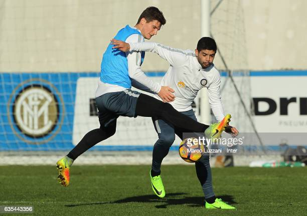 Ever Banega is challenged by Marco Andreolli during the FC Internazionale training session at the club's training ground Suning Training Center in...