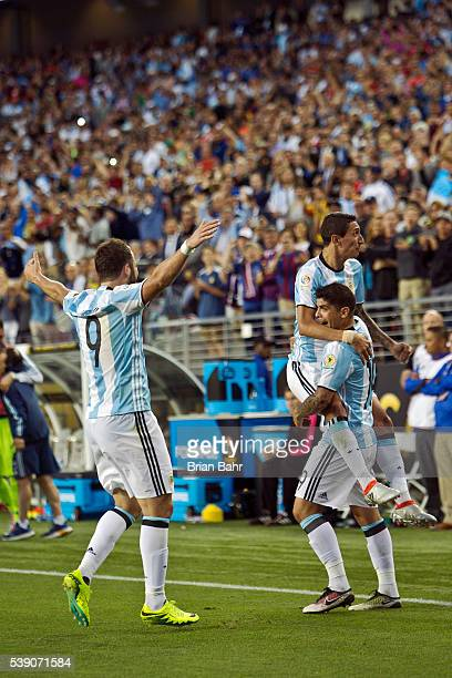 Ever Banega of Argentina celebrates a goal against Chile with his teammates Angel Di Maria and Gonzalo Higuain in the second half during a group D...