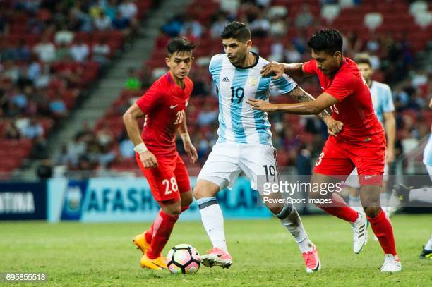 Ever Banega of Argentina fights for the ball with Izzdin Shafiq of Singapore during the International Test match between Argentina and Singapore at...