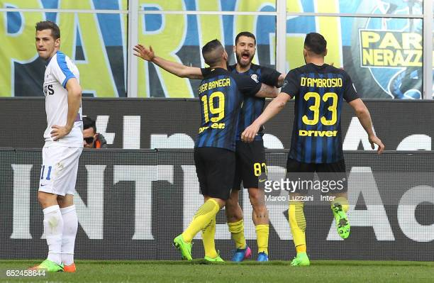 Ever Banega of FC Internazionale celebrates with Antonio Candreva and Danilo D'Ambrosio after scoring the third goal during the Serie A match between...