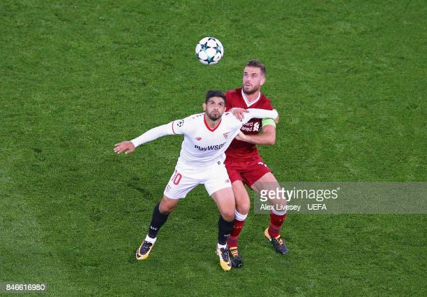 Ever Banega of Sevilla FC shields the ball from Jordan Henderson of Liverpool FC during the UEFA Champions League group E match between Liverpool FC...