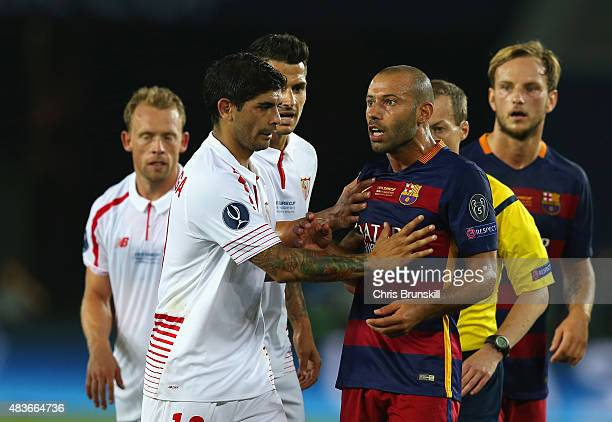 Ever Banega of Sevilla holds back Javier Mascherano of Barcelona during the UEFA Super Cup between Barcelona and Sevilla FC at Dinamo Arena on August...