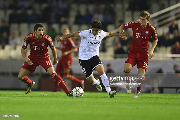 Ever Banega of Valencia batteles for the ball with Javi Martinez of Bayern Muenchen and his team mate Toni Kroos during the UEFA Champions League...