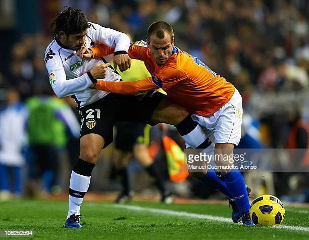 Ever Banega of Valencia duels for the ball with Duda of Malaga during the La Liga match between Valencia and Malaga at Estadio Mestalla on January 22...