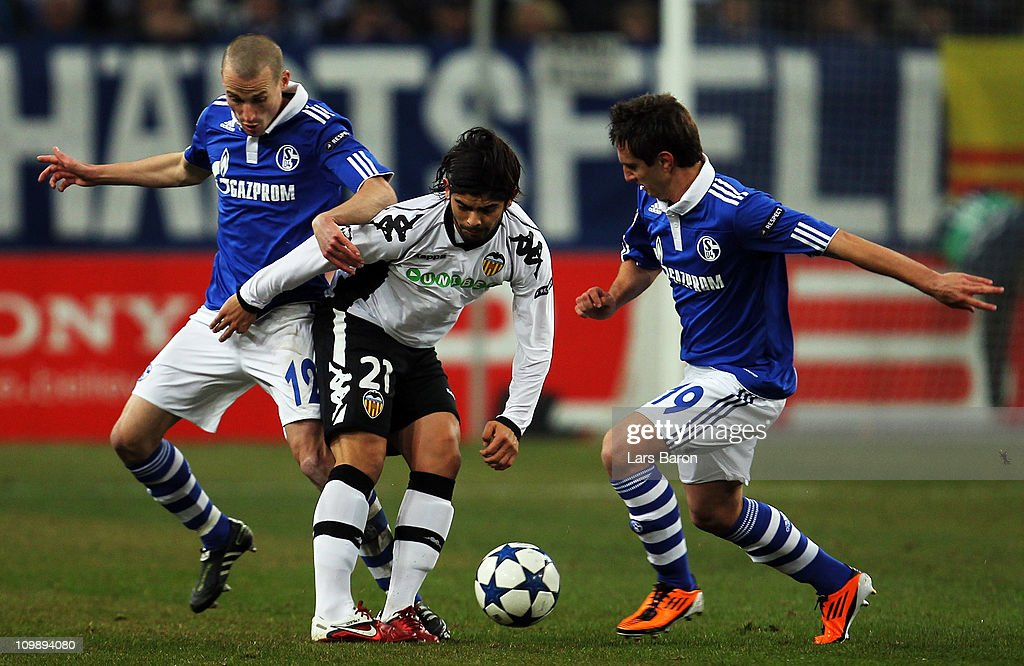 <a gi-track='captionPersonalityLinkClicked' href=/galleries/search?phrase=Ever+Banega&family=editorial&specificpeople=4100796 ng-click='$event.stopPropagation()'>Ever Banega</a> of Valencia is challenged by <a gi-track='captionPersonalityLinkClicked' href=/galleries/search?phrase=Peer+Kluge&family=editorial&specificpeople=635201 ng-click='$event.stopPropagation()'>Peer Kluge</a> (L) and Mario Gavranovic (R) of Schalke during the UEFA Champions League round of 16 second leg match between Schalke 04 and Valencia at Veltins Arena on March 9, 2011 in Gelsenkirchen, Germany.