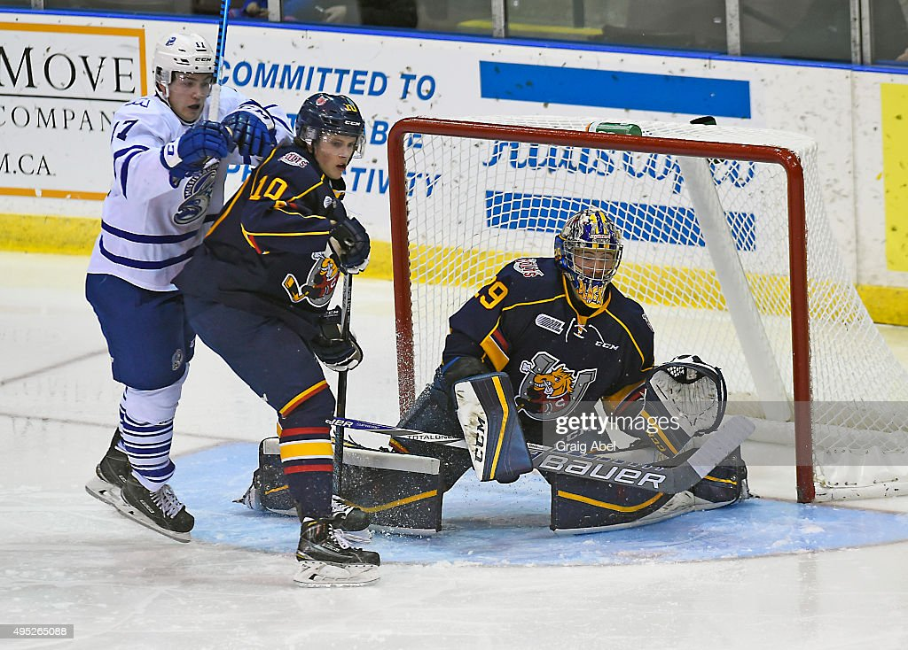 Everett Clark #17 of the Mississauga Steelheads fights for crease space with Justin Murray #10 and goalie Mackenzie Blackwood #29 of the Barrie Colts during OHL game action on November 1, 2015 at the Hershey Centre in Mississauga, Ontario, Canada.