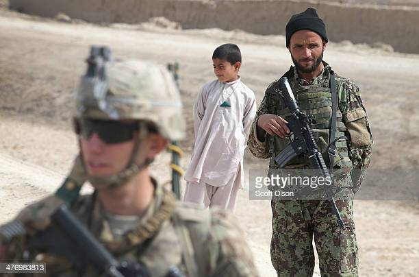 T J Everett from Osseo Wisconsin with the US Army's 4th squadron 2d Cavalry Regiment patrols through a village with soldiers from the Afghan National...
