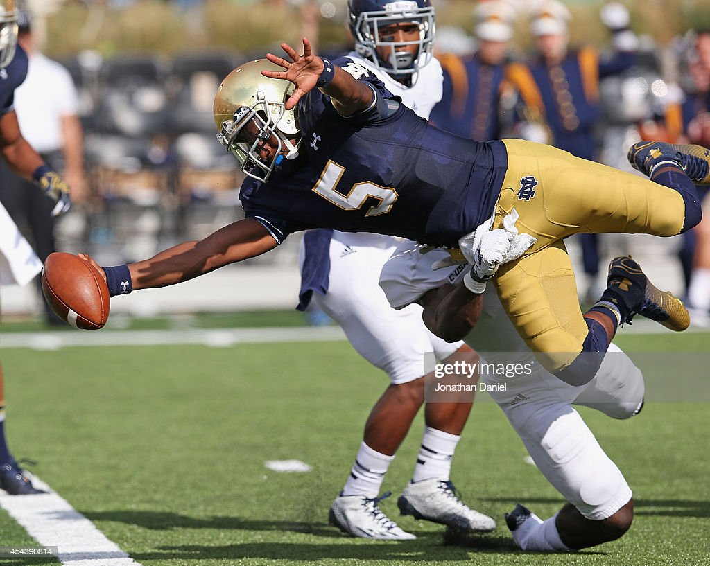 Everett Golson of the Norte Dame Fighting Irish dives into the end zone for a touchdown dragging Julius White of the Rice Owls at Notre Dame Stadium...