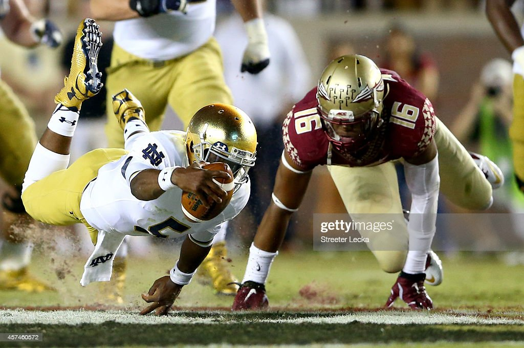 <a gi-track='captionPersonalityLinkClicked' href=/galleries/search?phrase=Everett+Golson&family=editorial&specificpeople=9688386 ng-click='$event.stopPropagation()'>Everett Golson</a> #5 of the Notre Dame Fighting Irish dives with the ball as Jacob Pugh #16 of the Florida State Seminoles tries to make the stop during their game at Doak Campbell Stadium on October 18, 2014 in Tallahassee, Florida.
