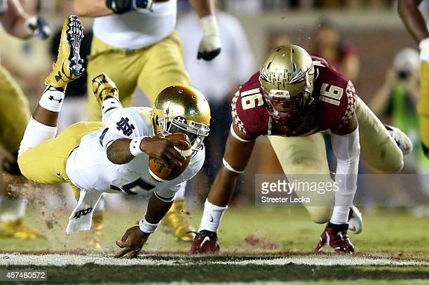 Everett Golson of the Notre Dame Fighting Irish dives with the ball as Jacob Pugh of the Florida State Seminoles tries to make the stop during their...