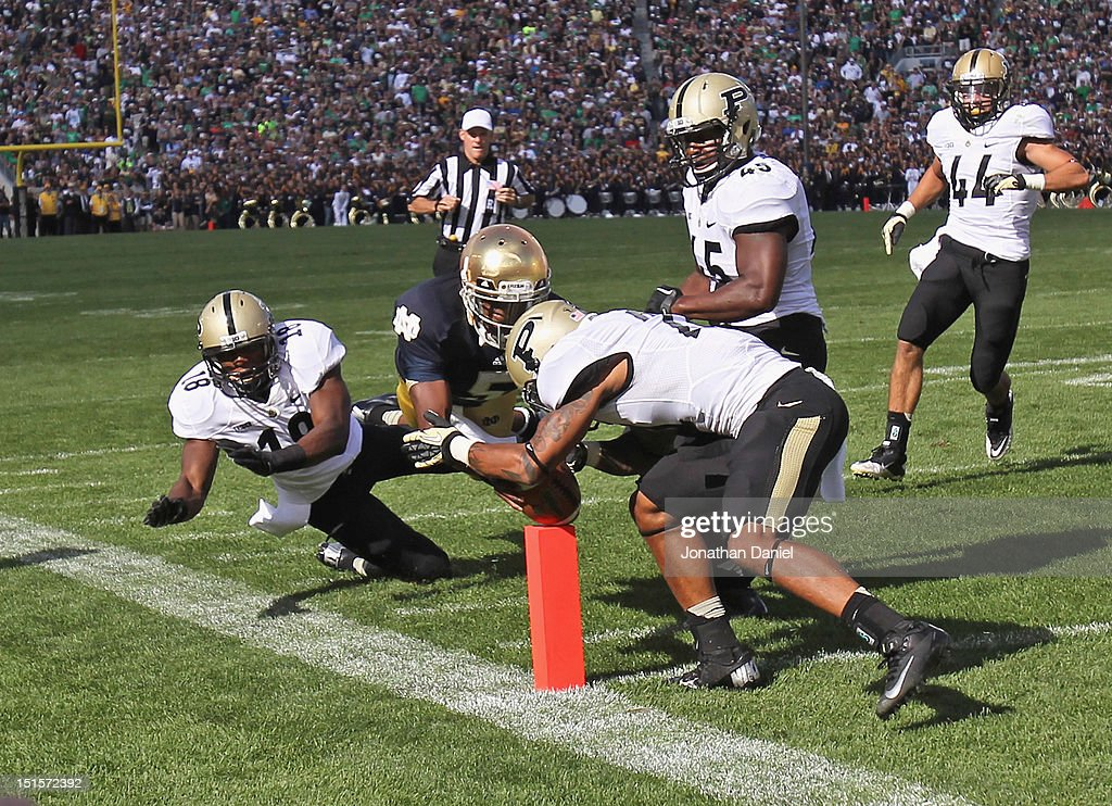 Everett Golson of the Notre Dame Fighting Irish hits the pylon with the ball for a touchdown as Ricardo Allen of the Purdue Boilermakers closes in at...