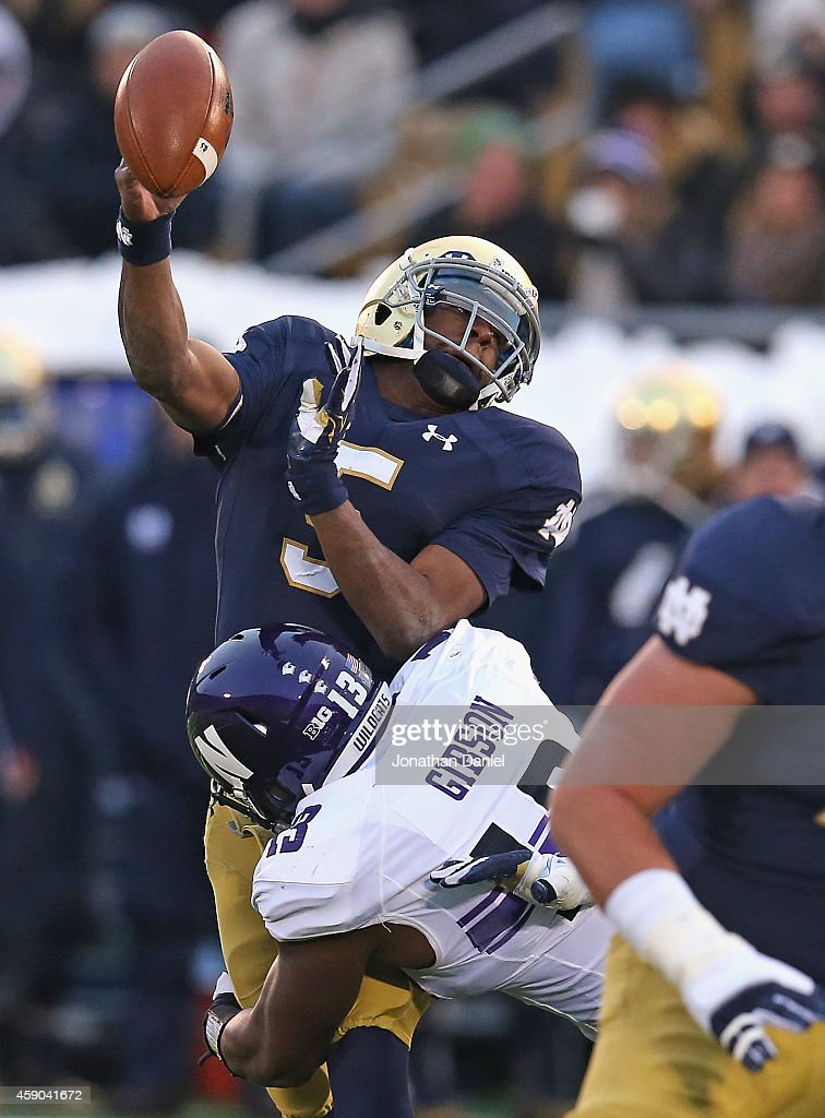 Everett Golson of the Notre Dame Fighting Irish is hit by Deonte Gibson 13 of the Northwestern Wildcats forcing a turnover at Notre Dame Stadium on...