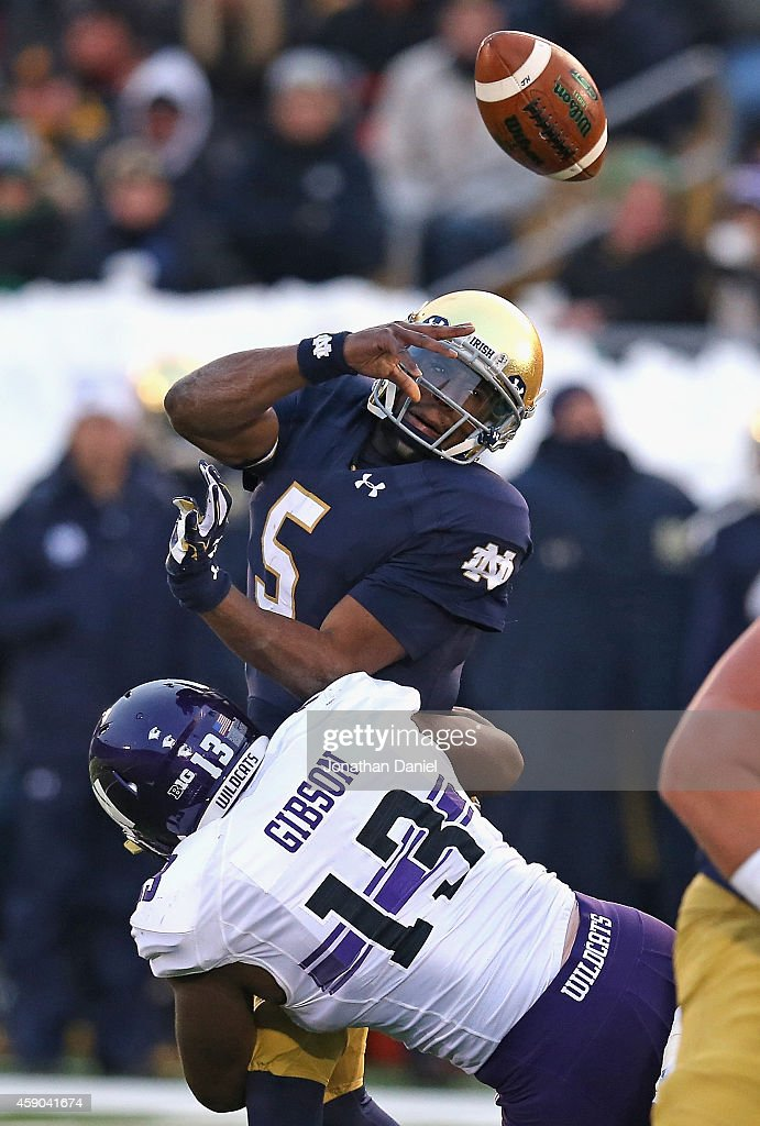 <a gi-track='captionPersonalityLinkClicked' href=/galleries/search?phrase=Everett+Golson&family=editorial&specificpeople=9688386 ng-click='$event.stopPropagation()'>Everett Golson</a> #5 of the Notre Dame Fighting Irish is hit by Deonte Gibson 13 of the Northwestern Wildcats forcing a turnover at Notre Dame Stadium on November 15, 2014 in South Bend, Indiana.