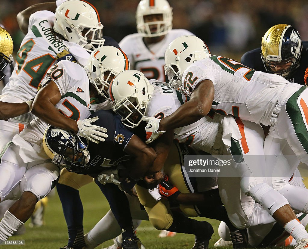<a gi-track='captionPersonalityLinkClicked' href=/galleries/search?phrase=Everett+Golson&family=editorial&specificpeople=9688386 ng-click='$event.stopPropagation()'>Everett Golson</a> #5 of the Notre Dame Fighting Irish is trackled by (L-R) A.J. Highsmith #30, Kacy Rodgers #22 and Denzel Perryman #52 of the Miami Hurricanes at Soldier Field on October 6, 2012 in Chicago, Illinois.