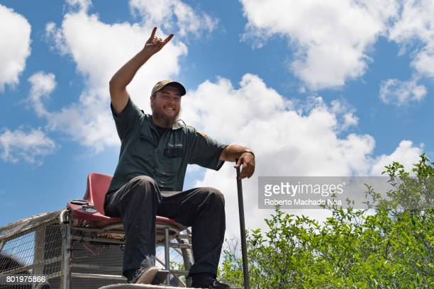 Everglades air boat operator Man in uniform on high seat showing the sign of horns with bright blue and cloudy sky above