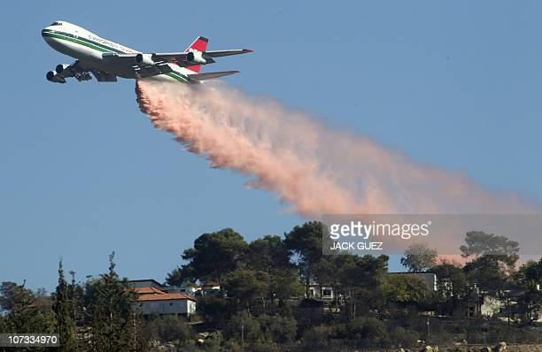 US Evergreen 747 supertanker sprays over an area in Ein Hod in the Carmel Forest in the outskirts of Haifa on December 5 2010 as dozens of...