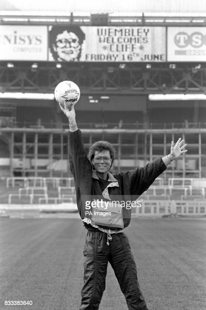 Evergreen pop star Cliff Richard holds up a football at Wembley Stadium where on the 16th June 1989 he celebrated 30 years of stardom with a special...