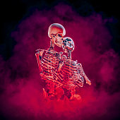 3D illustration of embracing male and female skeleton lovers surrounded by blazing inferno