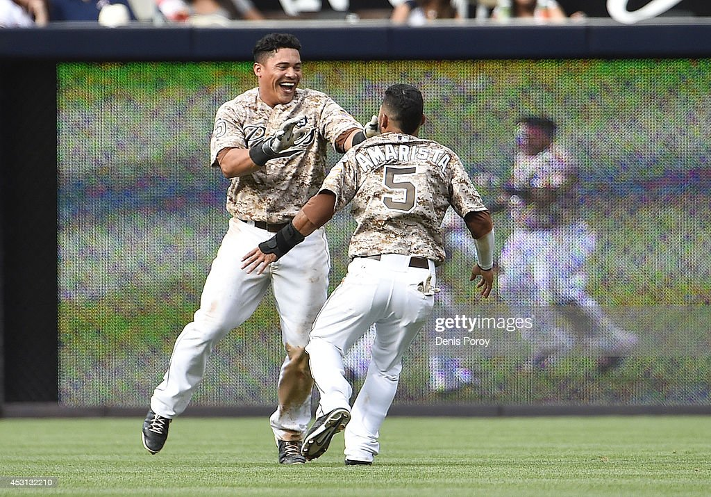 Everth Cabrera of the San Diego Padres celebrates his walkoff single with Alexi Amarista in the tenth inning of a baseball game against the Atlanta...