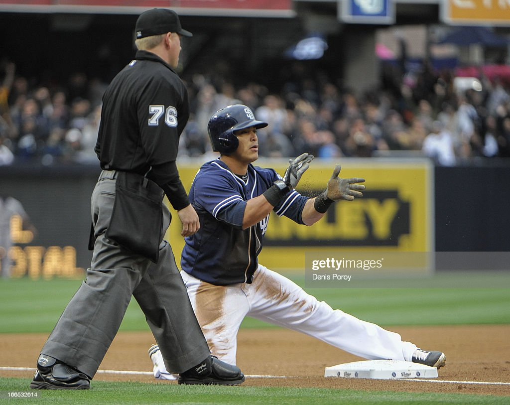 <a gi-track='captionPersonalityLinkClicked' href=/galleries/search?phrase=Everth+Cabrera&family=editorial&specificpeople=5743470 ng-click='$event.stopPropagation()'>Everth Cabrera</a> #2 of the San Diego Padres claps after sliding into third base with a triple as umpire Mike Muchlinski looks on during the first inning of a baseball game against the Colorado Rockies at Petco Park on April 13, 2013 in San Diego, California.