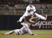 Everth Cabrera of the San Diego Padres jumps over Jordan Pacheco of the Colorado Rockies as he tries to turn a double play during the third inning of...