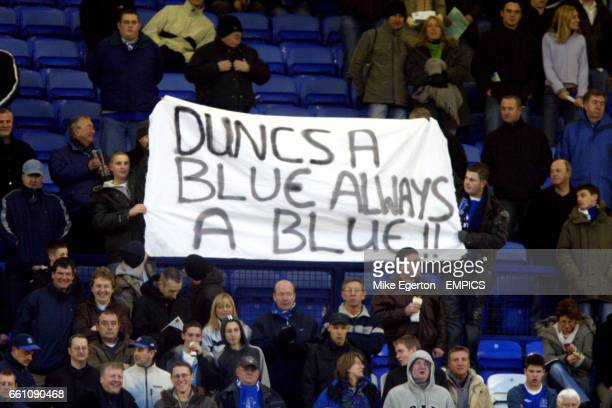A Everton fan holds a banner with a message refering Manchester United's Wayne Rooney about Duncan Ferguson