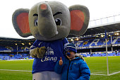 Everton fan Sam Dunne poses for a photograph with the Everton mascot before the Barclays Premier League match between Everton and Swansea City at...