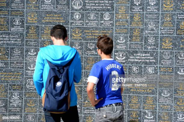 Everton fans in front of the wall of fame at Goodison Park