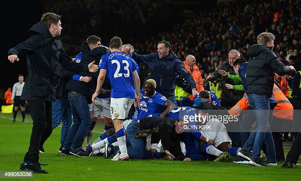 Everton fans mob Everton players on the pitch after English midfielder Ross Barkley scored his team's third goal during the English Premier League...