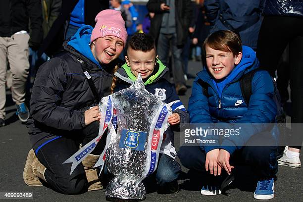 Everton fans pose for a picture with a replica FA Cup trophy before the FA Cup Fifth Round match between Everton and Swansea City at Goodison Park on...