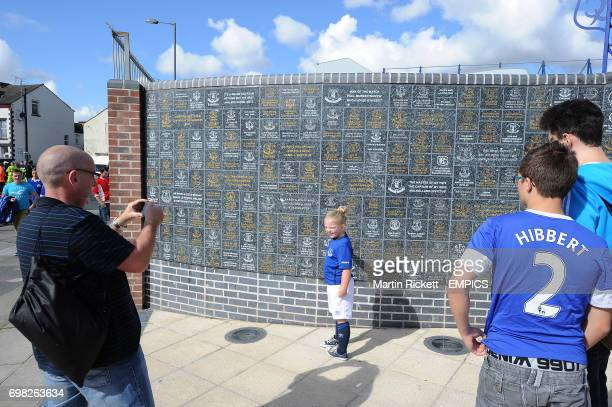 Everton fans pose for pictures in front of the wall of fame at Goodison Park