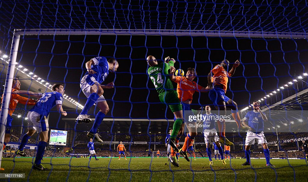 Everton keeper Tim Howard makes a save under pressure from Oldham attackers during the FA Cup Fifth Round Replay between Everton and Oldham Athletic at Goodison Park on February 26, 2013 in Liverpool, England.