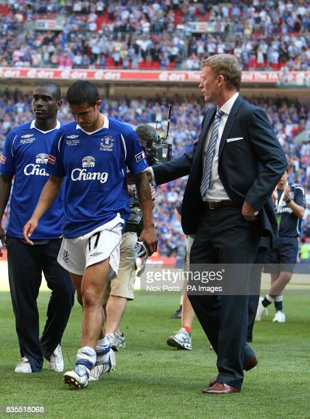 Everton manager David Moyes consoles Tim Cahill as the Chelsea players go up to collect the trophy