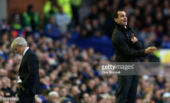 Everton manager Roberto Martinez gives instructions to his team as Stoke City manager Mark Hughes shows his dejection during the Barclays Premier...