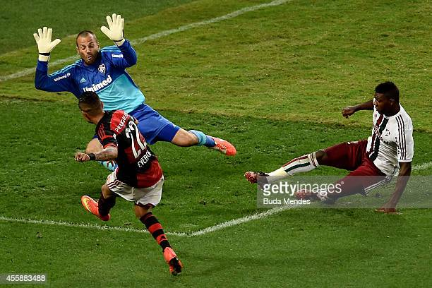Everton of Flamengo struggles for the ball with goalkeeper Diego Cavalieri and Elivelton of Fluminense during a match between Flamengo and Fluminense...