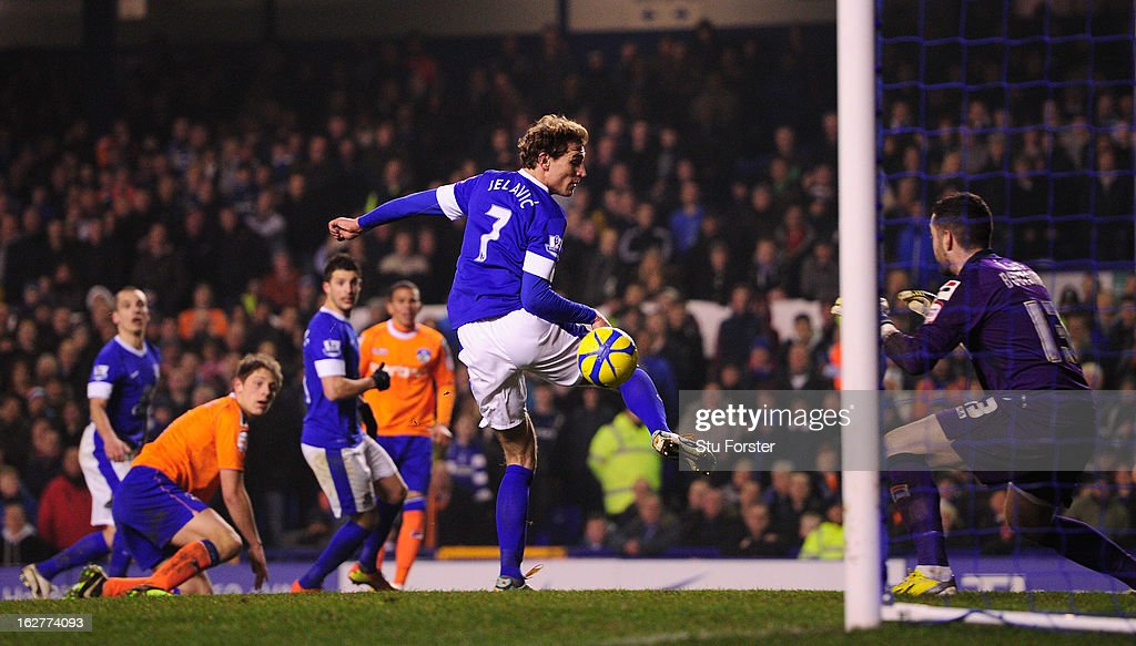 Everton player <a gi-track='captionPersonalityLinkClicked' href=/galleries/search?phrase=Leon+Osman&family=editorial&specificpeople=208939 ng-click='$event.stopPropagation()'>Leon Osman</a> (left) scores the third Everton goal past Oldham keeper Dean Bouzanis during the FA Cup Fifth Round Replay between Everton and Oldham Athletic at Goodison Park on February 26, 2013 in Liverpool, England.