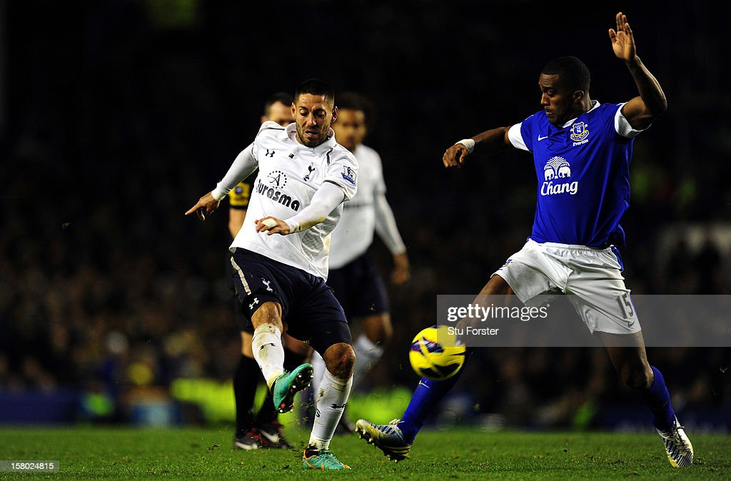 Everton player Sylvain Distin can only watch as Spurs player Clint Dempsey scores the opening goal during the Barclays Premier game between Everton and Tottenham Hotspur at Goodison Park on December 9, 2012 in Liverpool, England.