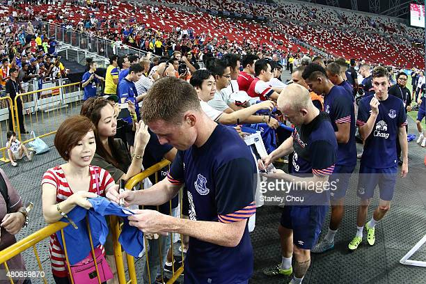 Everton players signs autographs at A 'golden circle' for Everton fans is seen during Everton FC open training session ahead of the match between...