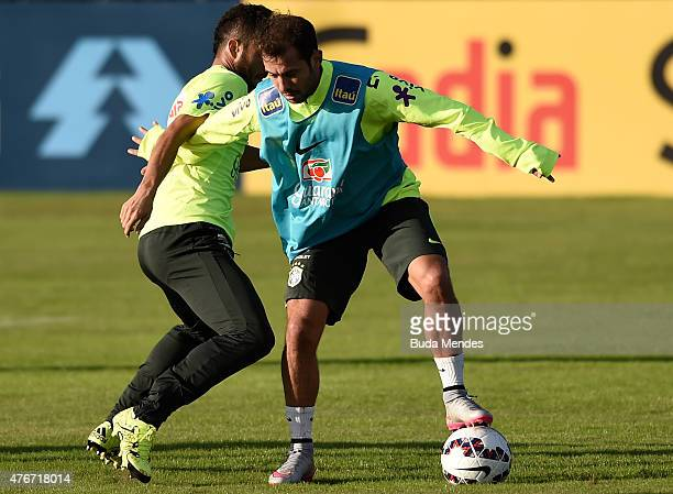 Everton Ribeiro and Marquinhos of Brazil in action during a training session at Hotel Vila Ventura on June 11 2015 in Viamao Brazil