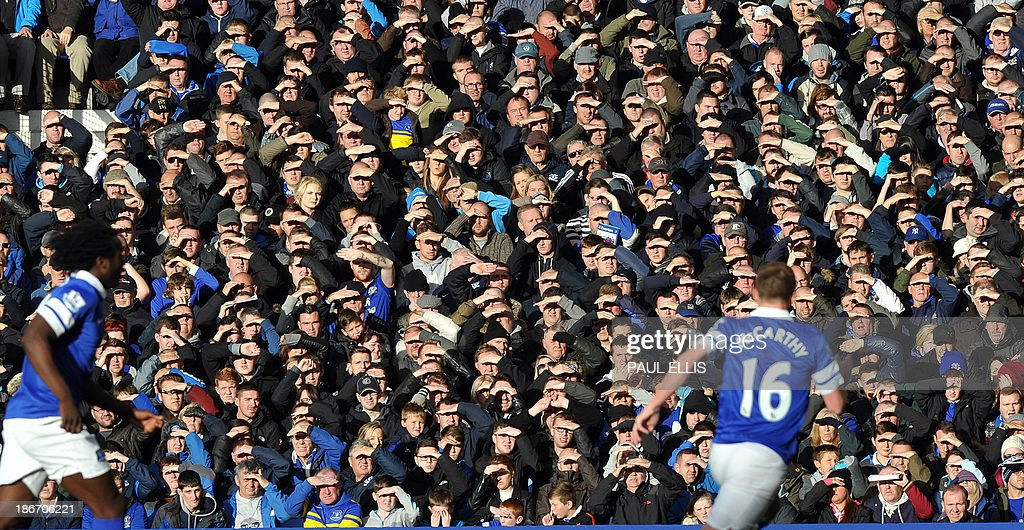 Everton supporters shield their eyes from the sun during the English Premier League football match between Everton and Tottenham Hotspur at Goodison Park in Liverpool, northwest England, on November 3, 2013. The game ended 0-0. AFP PHOTO / PAUL ELLIS USE. No use with unauthorized audio, video, data, fixture lists, club/league logos or live services. Online in-match use limited to 45 images, no video emulation. No use in betting, games or single club/league/player publications.