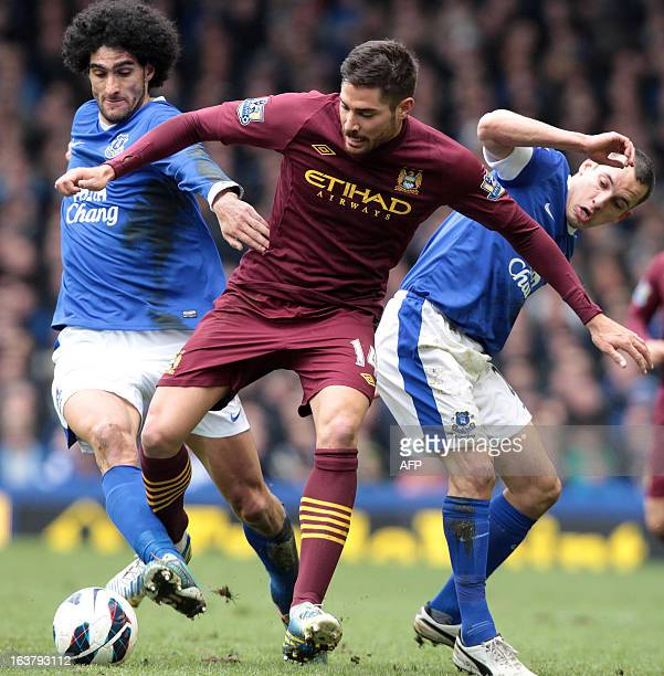 Everton's Belgian footballer Marouane Fellaini and English footballer Leon Osman tackle Manchester City's Spanish footballer Javier Garcia during...
