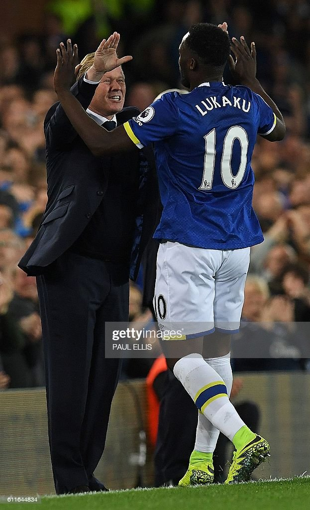 Everton's Belgian striker Romelu Lukaku (R) celebrates scoring his team's first goal with Everton's Dutch manager Ronald Koeman during the English Premier League football match between Everton and Crystal Palace at Goodison Park in Liverpool, north west England on September 30, 2016. / AFP / PAUL ELLIS / RESTRICTED TO EDITORIAL USE. No use with unauthorized audio, video, data, fixture lists, club/league logos or 'live' services. Online in-match use limited to 75 images, no video emulation. No use in betting, games or single club/league/player publications. /