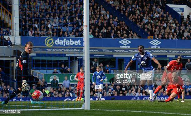 Everton's Belgian striker Romelu Lukaku shoots past Liverpool's Slovakian defender Martin Skrtel to score his team's first goal during of the English...