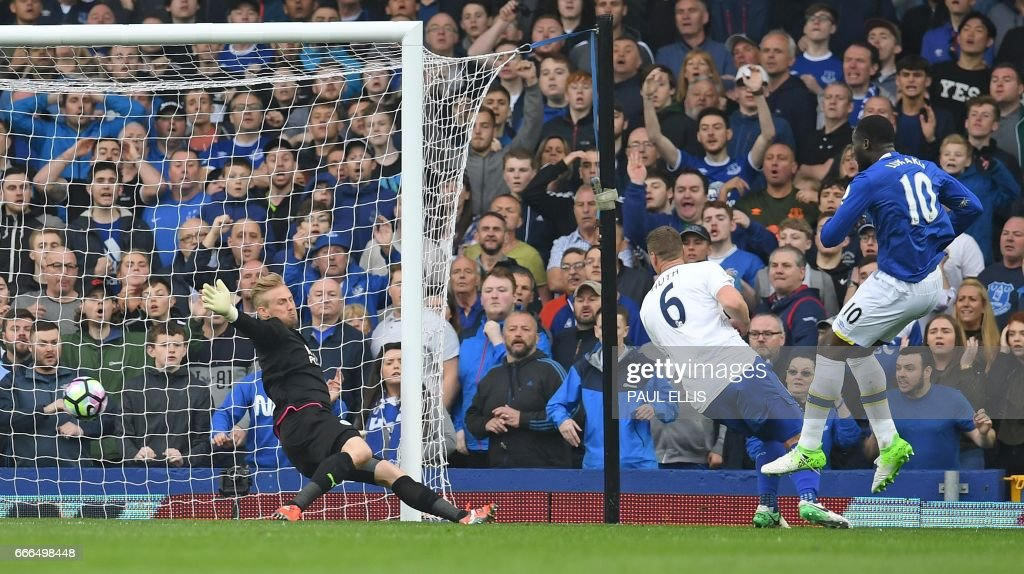 Everton's Belgian striker Romelu Lukaku (R) watches his shot pass Leicester City's Danish goalkeeper Kasper Schmeichel (L) to score his team's fourth goal during the English Premier League football match between Everton and Leicester City at Goodison Park in Liverpool, north west England on April 9, 2017. / AFP PHOTO / Paul ELLIS / RESTRICTED TO EDITORIAL USE. No use with unauthorized audio, video, data, fixture lists, club/league logos or 'live' services. Online in-match use limited to 75 images, no video emulation. No use in betting, games or single club/league/player publications. /